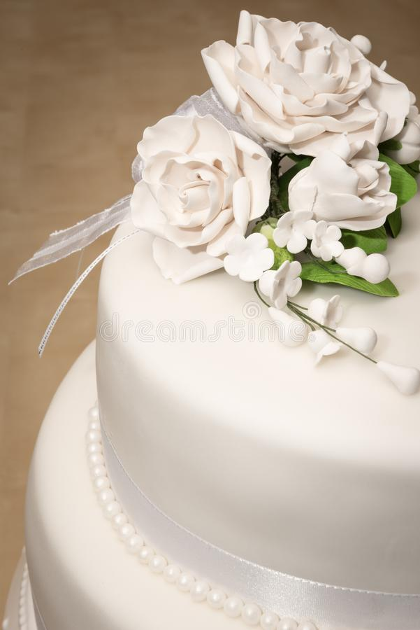 Wedding cake white with flowers and pearles. Wedding cake white with white flowers and pearles and a white fondant with a rose bouquet on the top stock images