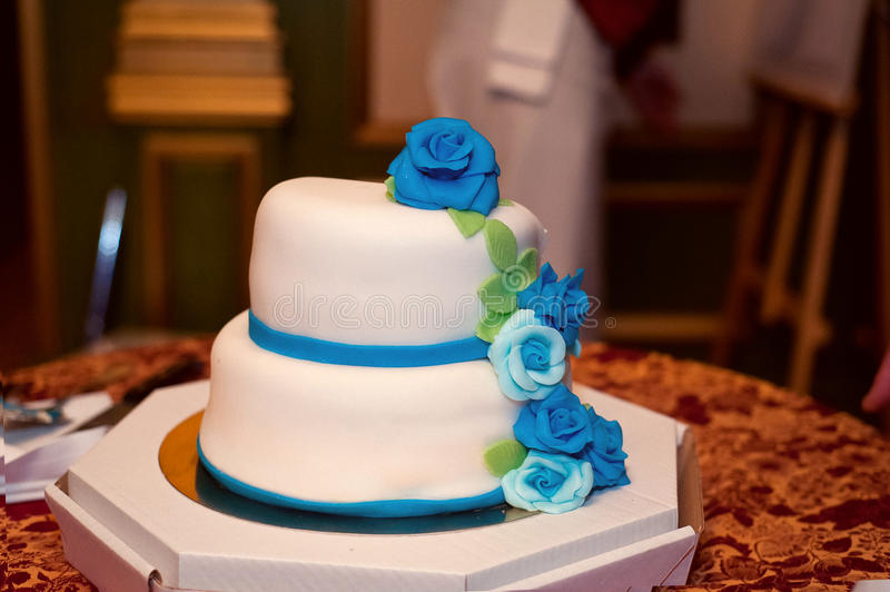 Wedding cake in white frosting with blue and turquoise roses. royalty free stock images