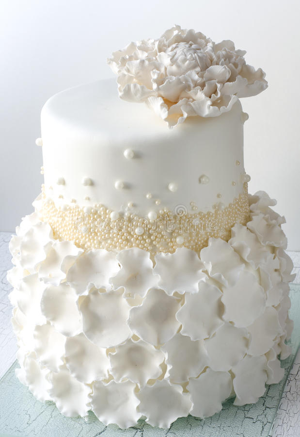 Wedding Cake. White Wedding Cake with white sugar peon and petals royalty free stock photo