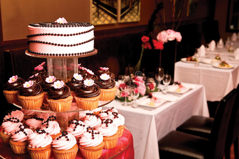 Wedding cakes. Selection of iced cupcakes on tiered table at a wedding royalty free stock image