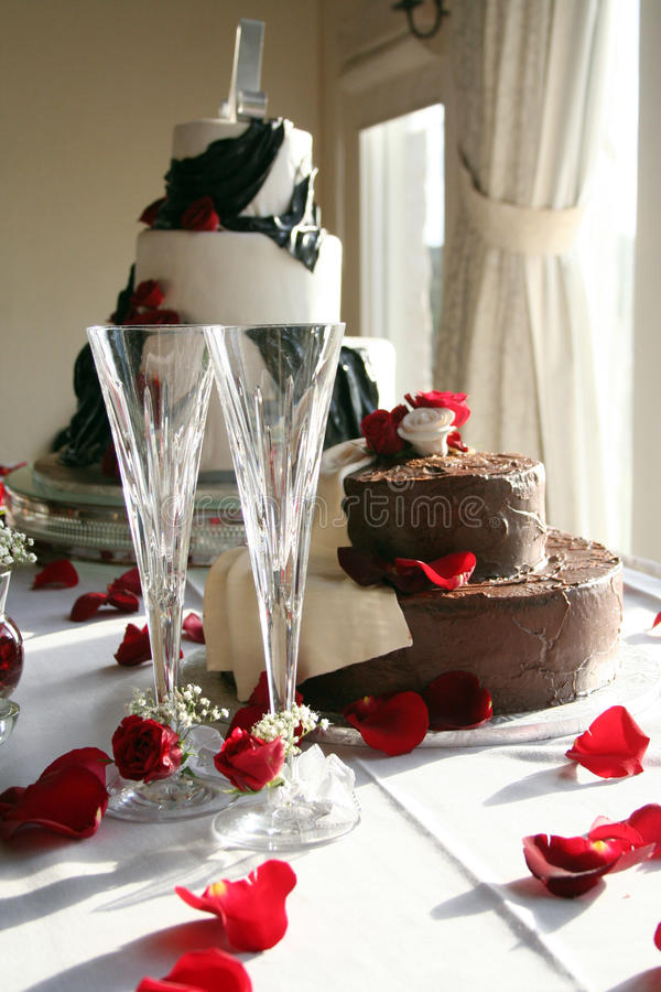 Wedding Cakes. The wedding cake and the groom's cake sit on a table in front of a big window stock image