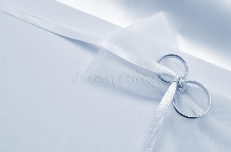 Wedding card. Wedding invitation card with rings and ribbon royalty free stock photo
