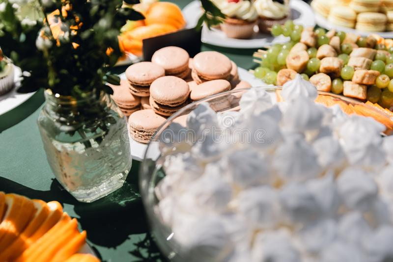 Wedding catering. Outdoors fourchette. Details of a festival catering: fruits, cupcakes, macaroons and burgers. Sweet table at the feast. Delicious candy bar at royalty free stock image