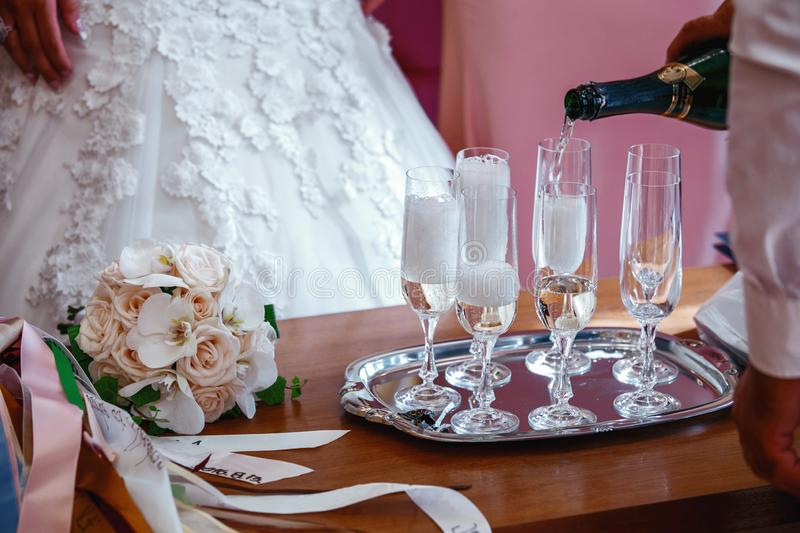 Wedding celebration with champagne. Happy, background. Wedding arrangement. Bridal bouquet, two glasses of champagne and a bottle of champagne on a wooden table royalty free stock photo