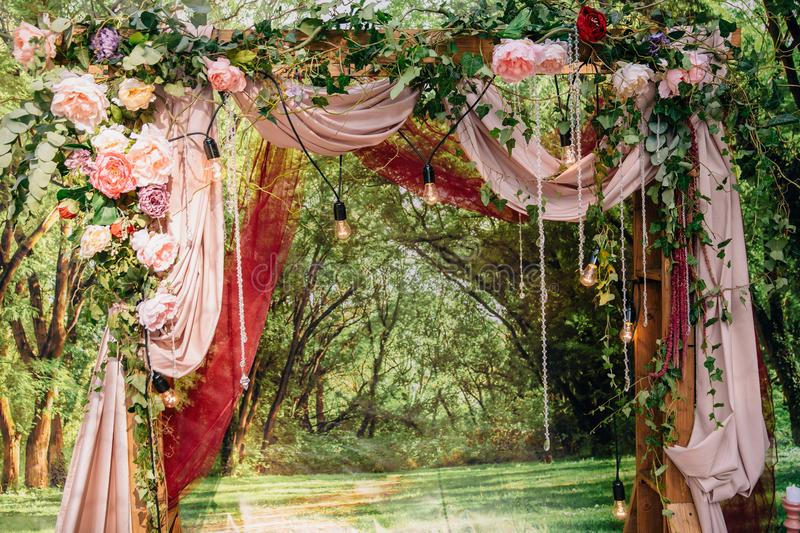 Wedding ceremony arch, altar decorated with flowers on the lawn royalty free stock photography