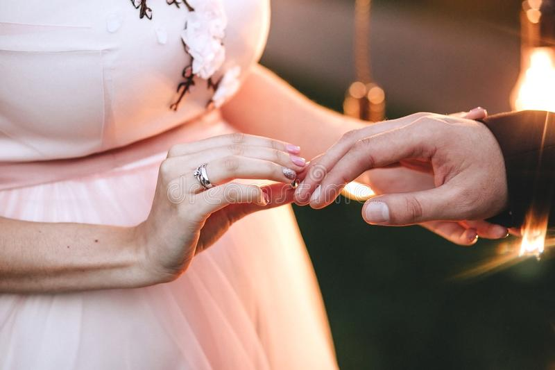 Wedding ceremony. The bride in a pink dress wears an engagement ring on a finger to the groom. On her hand is a gold ring with a d stock photo