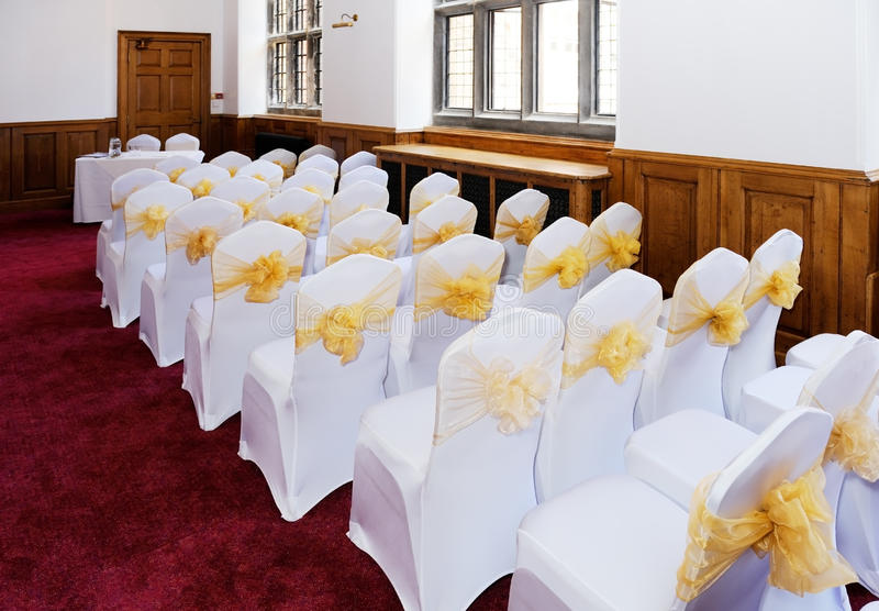 Wedding ceremony chairs. Wedding ceremony furniture and chairs with white covers and yellow ribbon royalty free stock image