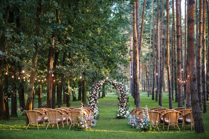 Wedding ceremony in the forest. A wedding ceremony in the pine forest awaits the appearance of guests. The arch is made of flowers of roses, wicker chairs stand stock images