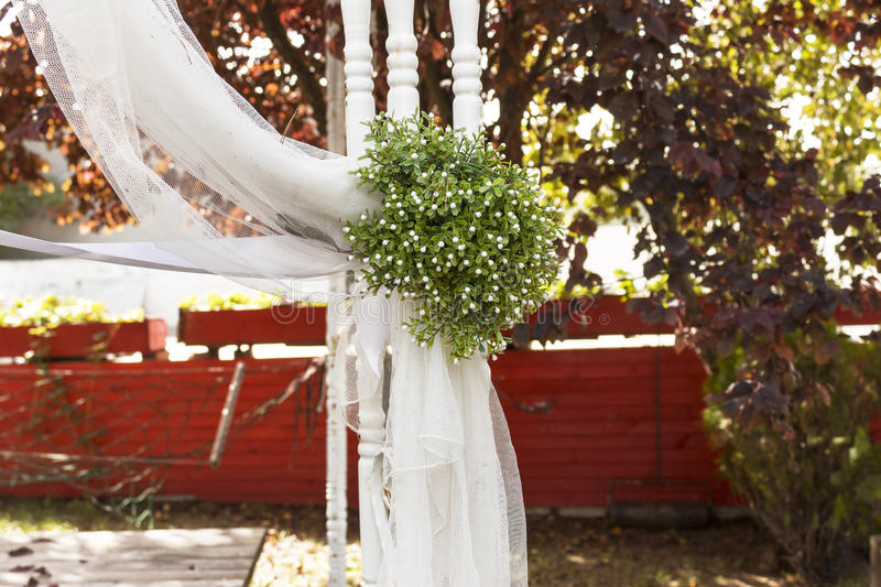 Wedding ceremony. Wedding garnish such as flower bouquet, tulle fabric and bower in garden royalty free stock image