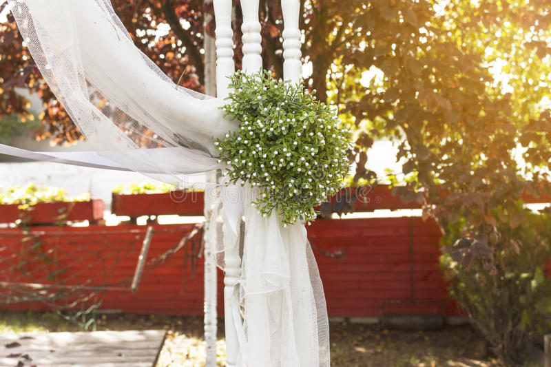 Wedding ceremony. Wedding garnish such as flower bouquet, tulle fabric and trellis in garden stock images