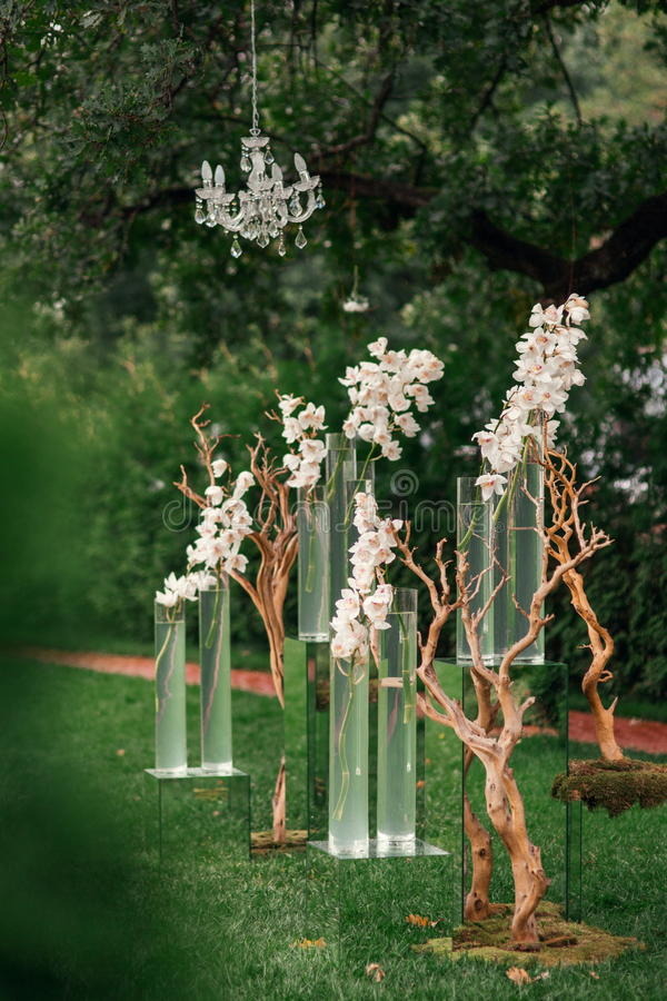 Wedding ceremony orchid flowers decor. Outdoor Wedding ceremony decoration with orchid flowers and vase royalty free stock image