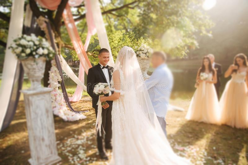 Wedding ceremony outside. Groom and bride standing by the big tree. Decoration in the park. Background of lake royalty free stock photo