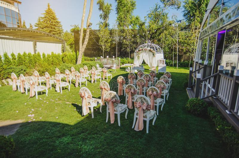 Wedding ceremony place decorated with roses,. Ranunculus and peony and vintage furniture chairs, table on sunset stock image