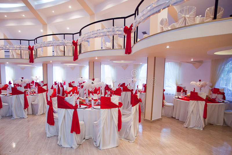 Wedding ceremony saloon. Wedding saloon having tables with white tablecloth and red decorations stock photography