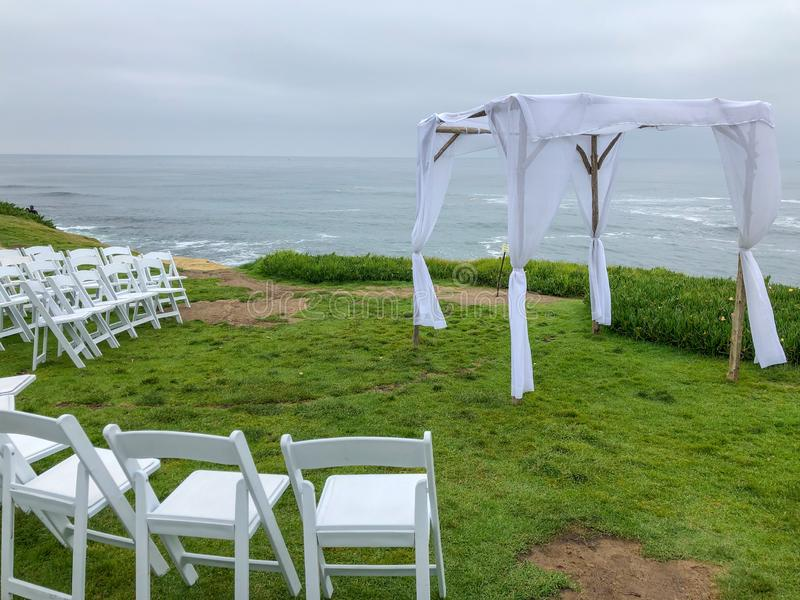 Wedding ceremony setting in the garden in front of the ocean. Wedding ceremony setting with white chairs and arch in the garden in front of the ocean, wedding royalty free stock photo