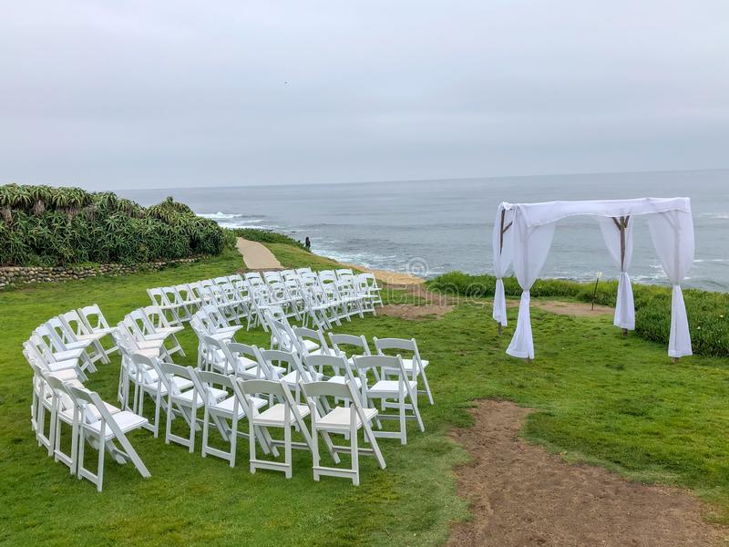 Wedding ceremony setting in the garden in front of the ocean. Wedding ceremony setting with white chairs and arch in the garden in front of the ocean, wedding royalty free stock images