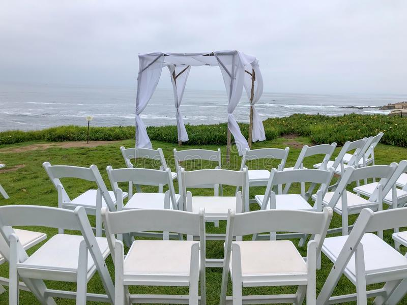 Wedding ceremony setting in the garden in front of the ocean. Wedding ceremony setting with white chairs and arch in the garden in front of the ocean, wedding stock photography