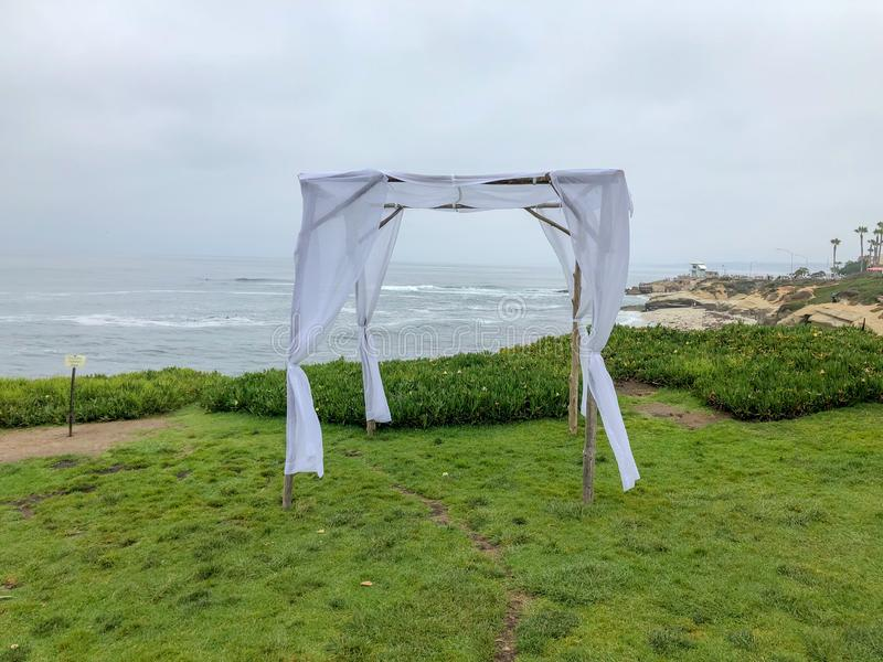 Wedding ceremony setting in the garden in front of the ocean. Wedding ceremony setting with white chairs and arch in the garden in front of the ocean, wedding royalty free stock photos
