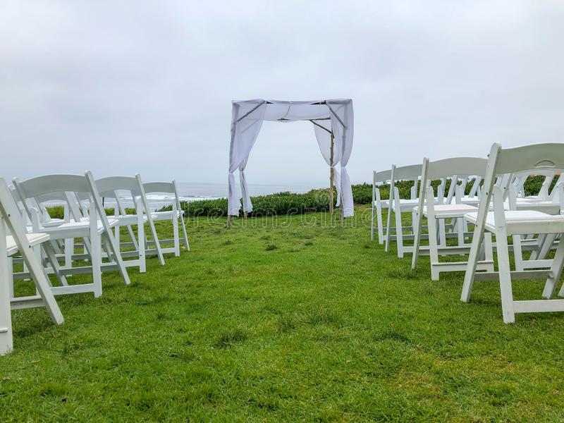 Wedding ceremony setting in the garden in front of the ocean. Wedding ceremony setting with white chairs and arch in the garden in front of the ocean, wedding royalty free stock image
