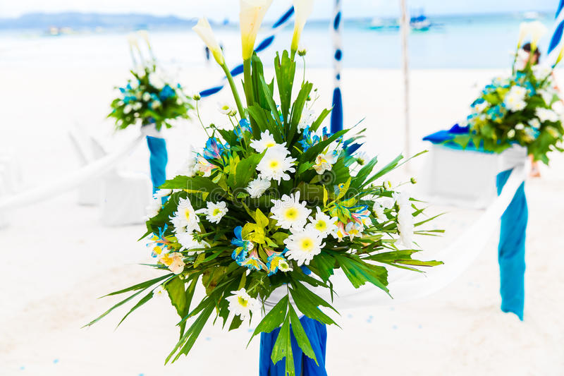 Wedding ceremony on a tropical beach in blue. Arch decorated wit. H flowers on the sandy beach. Wedding and honeymoon concept stock image