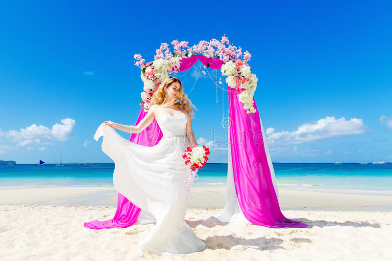 Wedding ceremony on a tropical beach in purple. Happy blond bride with wedding bouquet under the arch decorated with flowers on t royalty free stock images