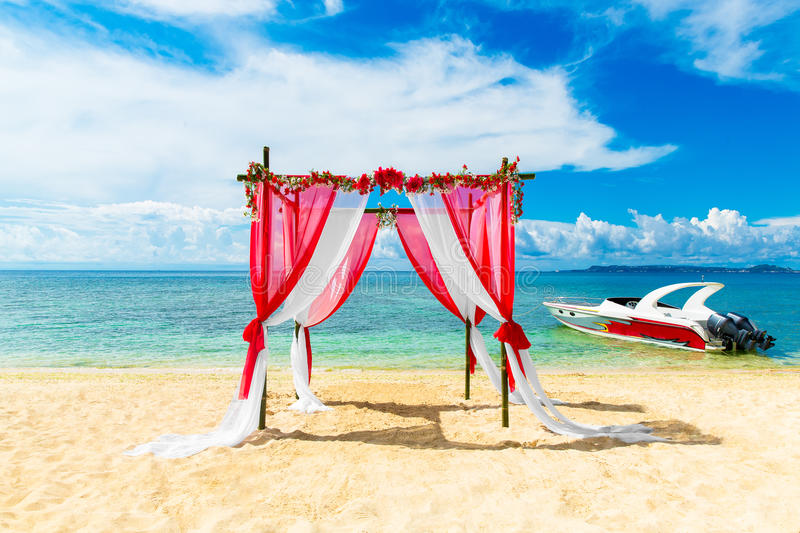 Wedding ceremony on a tropical beach in red. Arch decorated with flowers. On the sandy beach. Wedding and honeymoon concept royalty free stock image