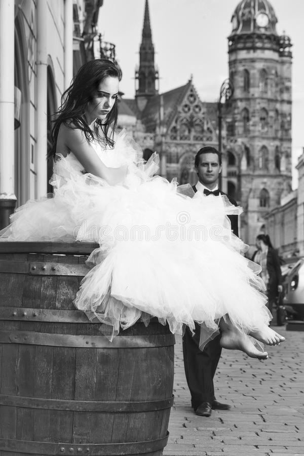 Wedding ceremony. wedding couple on wooden barrel near castle. Wedding ceremony. young wedding couple of girl with brunette hair and pretty face in white bride royalty free stock photo