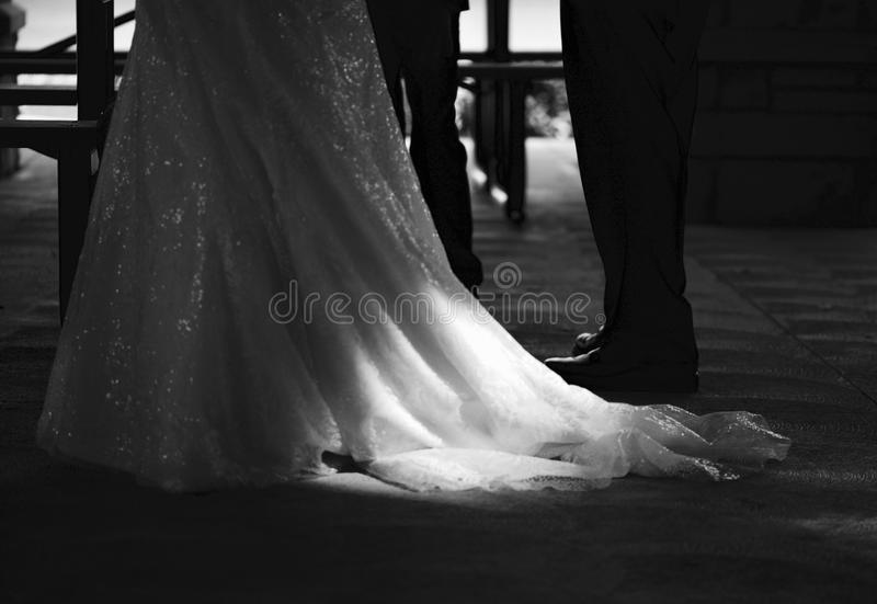 A white wedding dress lays on the ground and is illuminated by natural sunlight - WEDDING DRESS stock photo