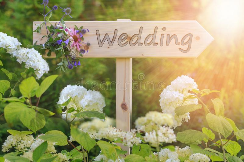 Wedding ceremony wooden sign with a bouquet of wildflowers on a background of white hydrangeas stock images