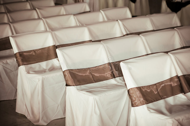 Wedding chair covers. Chairs lined up for a wedding ceremony with covers royalty free stock images