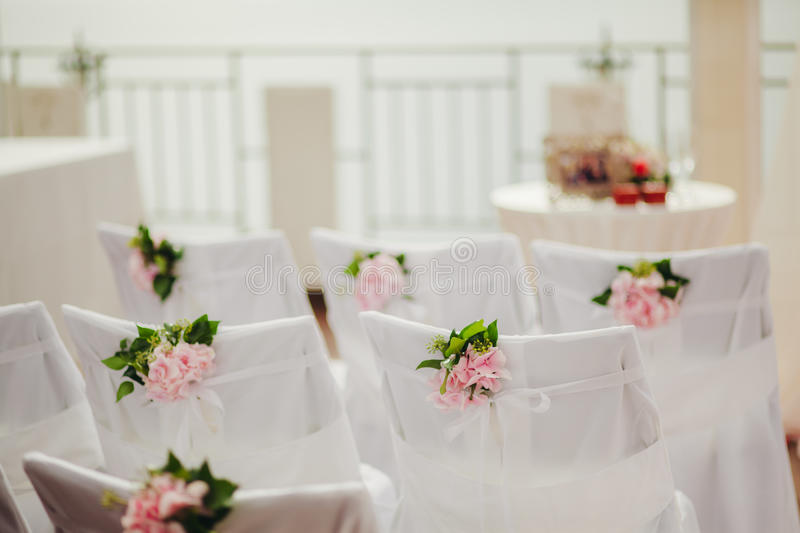 Wedding chair covers with pink flowers. At wedding day royalty free stock photo