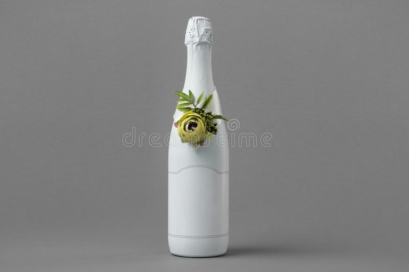 Wedding champagne bottle with blank label. Bottle decorated with roses, pearls and ribbon. Copy space for text stock photos