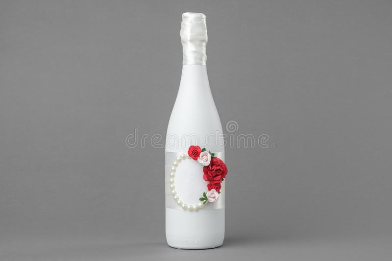 Wedding champagne bottle decorated with roses, pearls and and ribbon. Copy space for text royalty free stock photos
