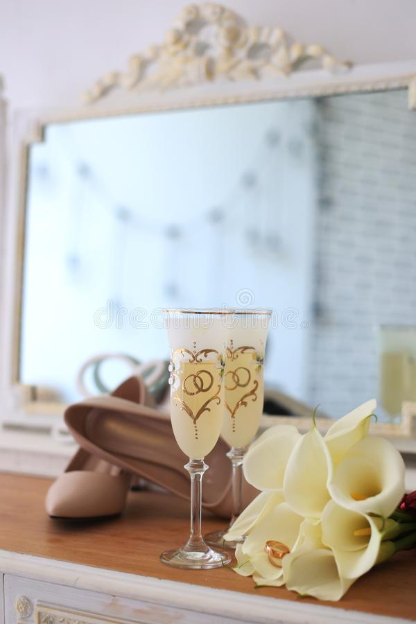 Wedding champagne glasses, wedding rings in white callas flowers, shoes and a mirror in the background stock photography