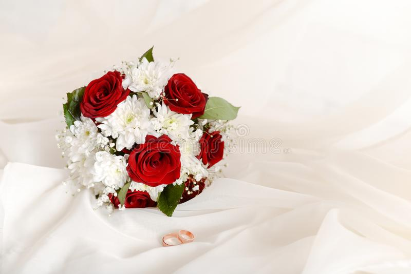 Wedding concept bouquet of red roses and wedding gold rings on light pastel background. copy space stock photo