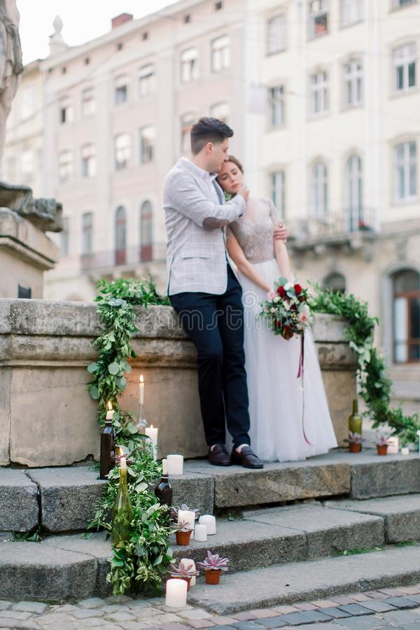 Wedding concept. The happy romantic wedding couple are standing on the stone stairs in front of old city buildings royalty free stock photography