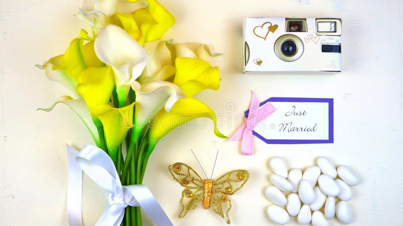 Wedding concept overhead flat lay with bouquet, camera, and sweet almonds. royalty free stock image