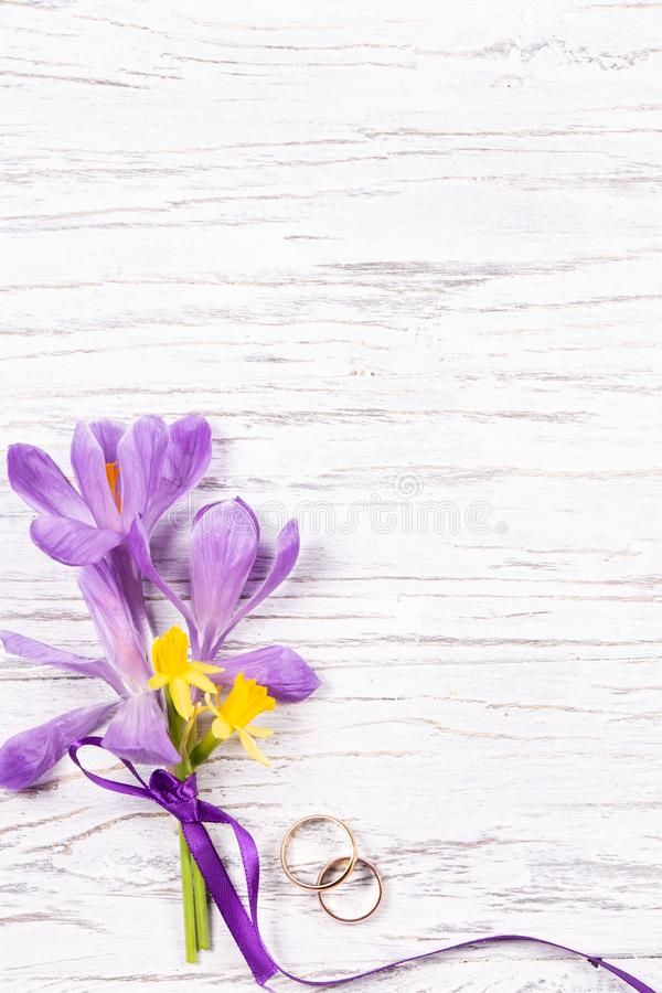Wedding concept with spring flowers and two golden rings stock image