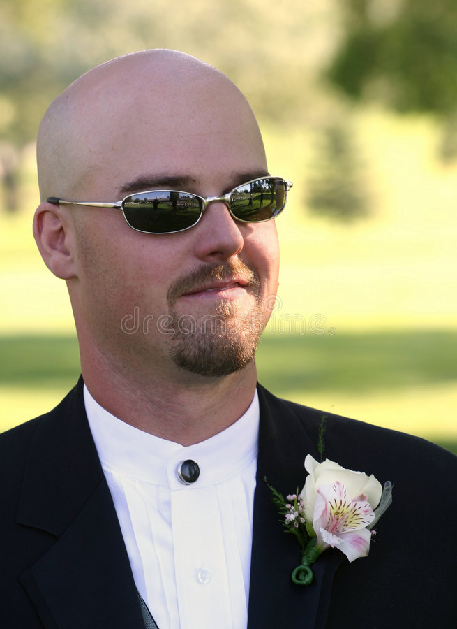 Wedding Cool Groom. A dapper bald groom in a black tux with cool sunglasses awaits his bride at the wedding ceremony. He wears a corsage and smiles. Of course stock image