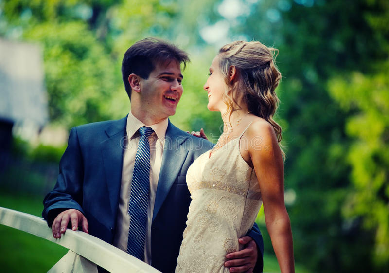 Wedding couple. Smiling Wedding couple on a bridge in a park royalty free stock photography