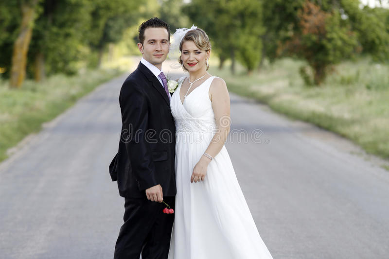 Wedding couple. Young attractive wedding couple posing on a road