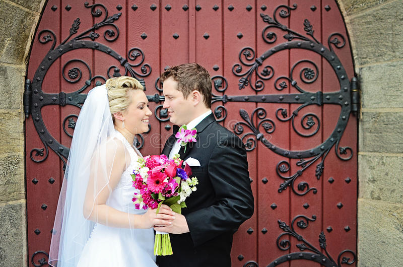 Wedding couple. A bride and groom looking at one another in front of an ornate door. Formal wedding royalty free stock images