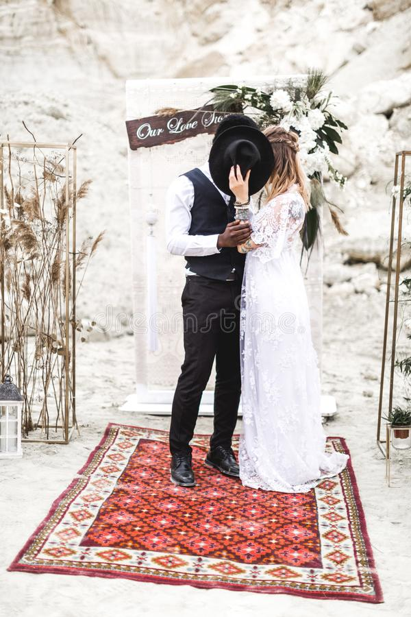 Wedding couple, African man and Caucasian woman, dressed in boho style are staying before the wedding arch, kissing nd stock images