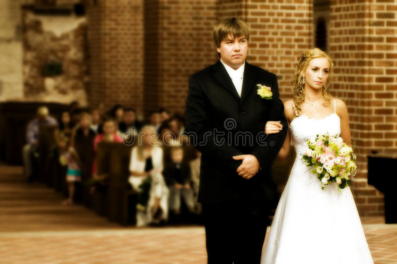 Wedding couple at the altar. In a church with relatives in the background stock images
