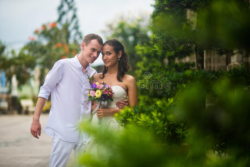 Wedding couple, a beautiful young bride and groom, are standing in the Park outdoors, embracing and and smiling royalty free stock photos