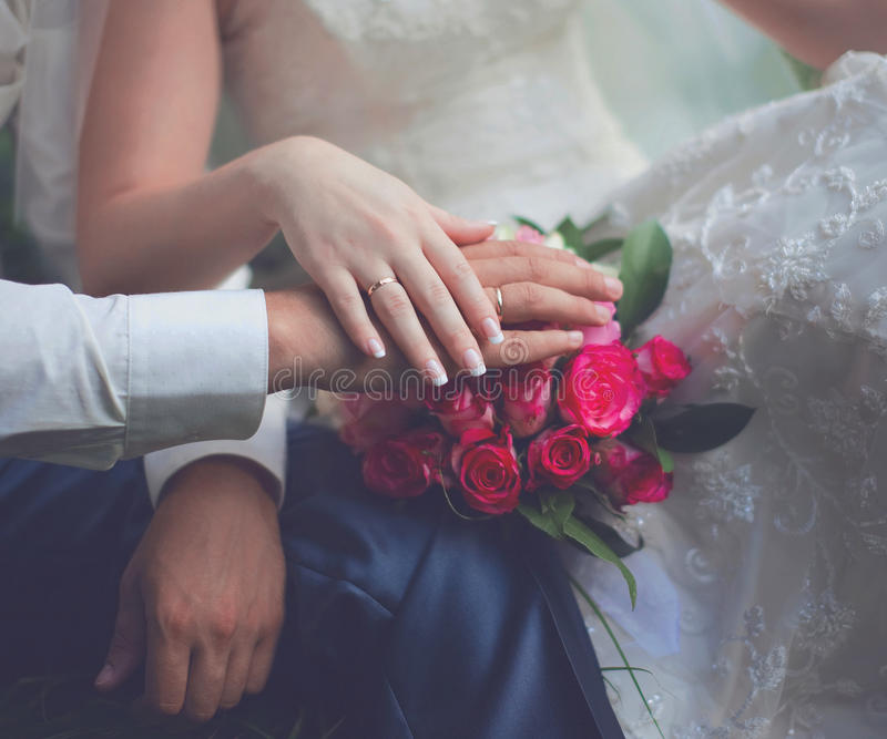 Wedding couple, bride and groom, hands with rings and pink gentle bouquet flowers closeup, country, rustic style stock photo