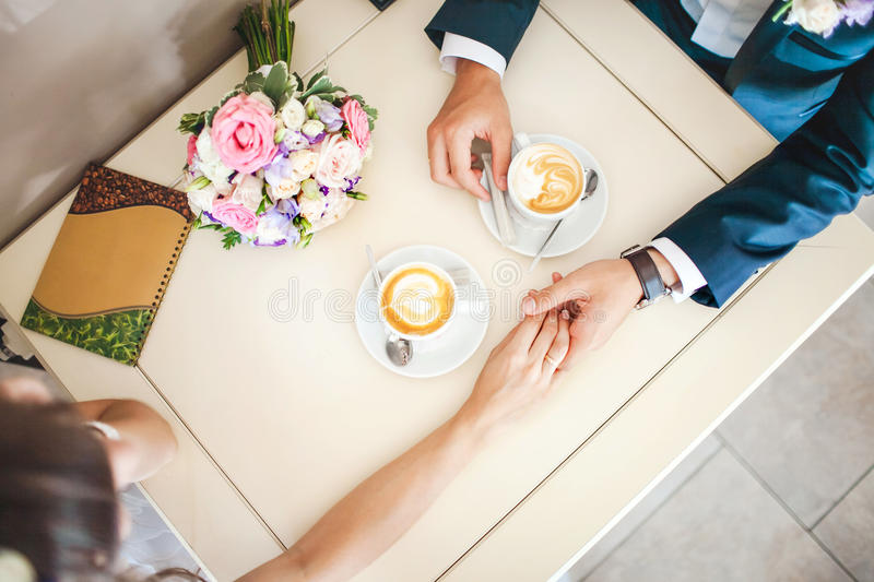 Wedding couple at cafe, top view. Man holds woman's hand, drinks espresso. Bride and groom coffee break dating gift. Wedding couple at the cafe, top view. Man royalty free stock image