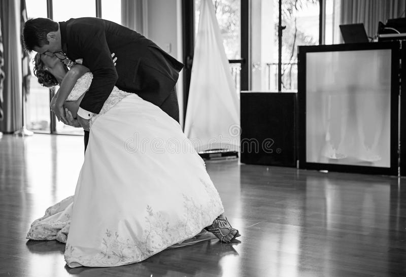 Wedding couple dancing. A groom dipping his bride during first wedding dance stock photo