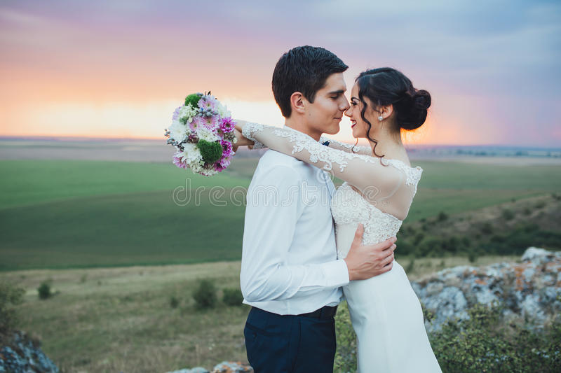 Wedding couple. In the evening. Peaceful romantic moment. Happy bride and groom on a beautiful beach on sunset. bride in a white dress holding a bouquet of stock image