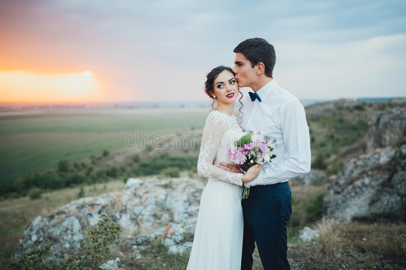 Wedding couple. In the evening. Peaceful romantic moment. Happy bride and groom on a beautiful beach on sunset. bride in a white dress holding a bouquet of stock photos